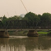 Old Iron Bridge crossing the River Ping, Chiang Mai. River Market Restaurant on Right Bank (Red Roof)
