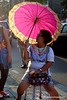 Woman on a chair with a pinlk umbrella made translucent by the setting sun in Bangkok , Thailand in February 2014