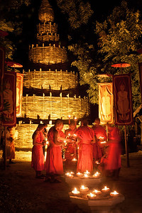 Buddhist Thai monks lighting candles in front of a bamboo stupa during Visakha Bucha in Chiang Mai, Thailand.