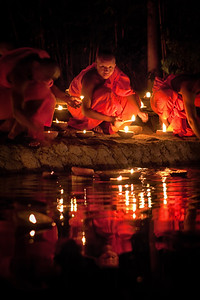 A young monk lighting a candle during Visakha Bucha in Chiang Mai, Thailand.