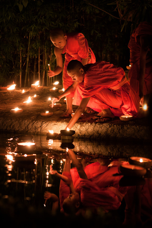 Young monks lighting up candles during Visakha Bucha in Chiang Mai, Thailand.