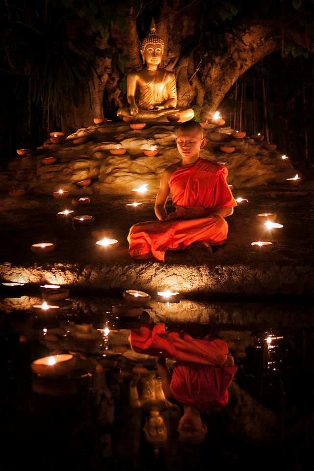 A young meditating monk next to a Buddha statue during Visakha Bucha in Chiang Mai, Thailand.