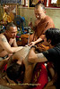Luang Pi Nunn Applies A Sak Yant Tattoo On A Devotee's Back At Wat Bang Phra