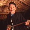 Elderly Lisu man plays stringed instrument, Pai area, Thailand.