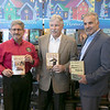 Fitchburg Mayor Stephen DiNatale, left, and Leominster Mayor Dean Mazzarella stand with author Mark Bodanza, center, who wrote the book on their rivalry at the Thanksgiving rivalry fundraiser held at Barnes & Noble in Leominster on Saturday, Nov. 23, 2019. SENTINEL & ENTERPRISE/JOHN LOVE