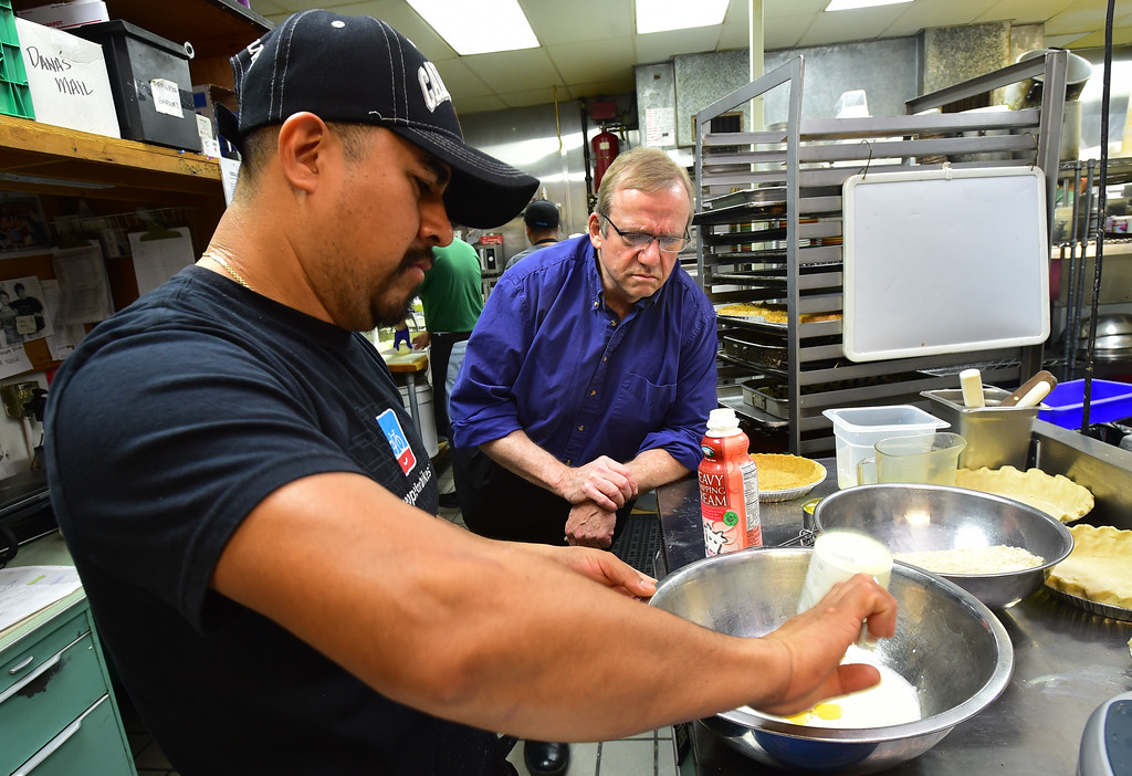 . John Lehndorff watches Raymundo Aparicio put together ingredients as he mades pies in the kitchen at the Walnut Cafe in Boulder on Monday. Paul Aiken Staff Photographer Nov 13, 2017
