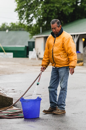 A stablehand fills a bucket with water at Churchill Downs on Saturday. Staff Photo By Josh Hicks