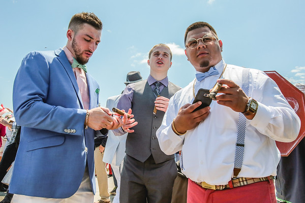 Three fans wear bold suits and smoke celebratory cigars in the infield at the 143rd Kentucky Derby at Churchill Downs on Saturday. Staff Photo By Josh Hicks