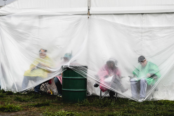 Fans take cover while it rains during the early hours of the 143rd Kentucky Derby at Churchill Downs on Saturday. Staff Photo By Josh Hicks