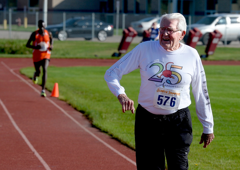 . Ken Wright, 88, finishes the 2-mile run about the same time as 10k winner, Simon Ndirangu (background), finishes at  the annual Sunrise Stampede 2-mile and 10K  races held at Silver Creek High School in Longmont.  For more photos, go to dailycamera.com.  Cliff Grassmick  Staff Photographer August 12, 2017