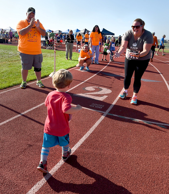 . Quinn Carton, 2, runs toward his mother, Jessica Hirsch-Carton, at the finish line of the 2-mile race of  the annual Sunrise Stampede 2-mile and 10K  races held at Silver Creek High School in Longmont.  For more photos, go to dailycamera.com.  Cliff Grassmick  Staff Photographer August 12, 2017
