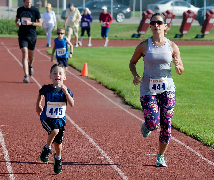 . Lance Reid, 5, and his mother, Holly, finish the 2-mile run of the annual Sunrise Stampede 2-mile and 10K  races held at Silver Creek High School in Longmont.  For more photos, go to dailycamera.com.  Cliff Grassmick  Staff Photographer August 12, 2017