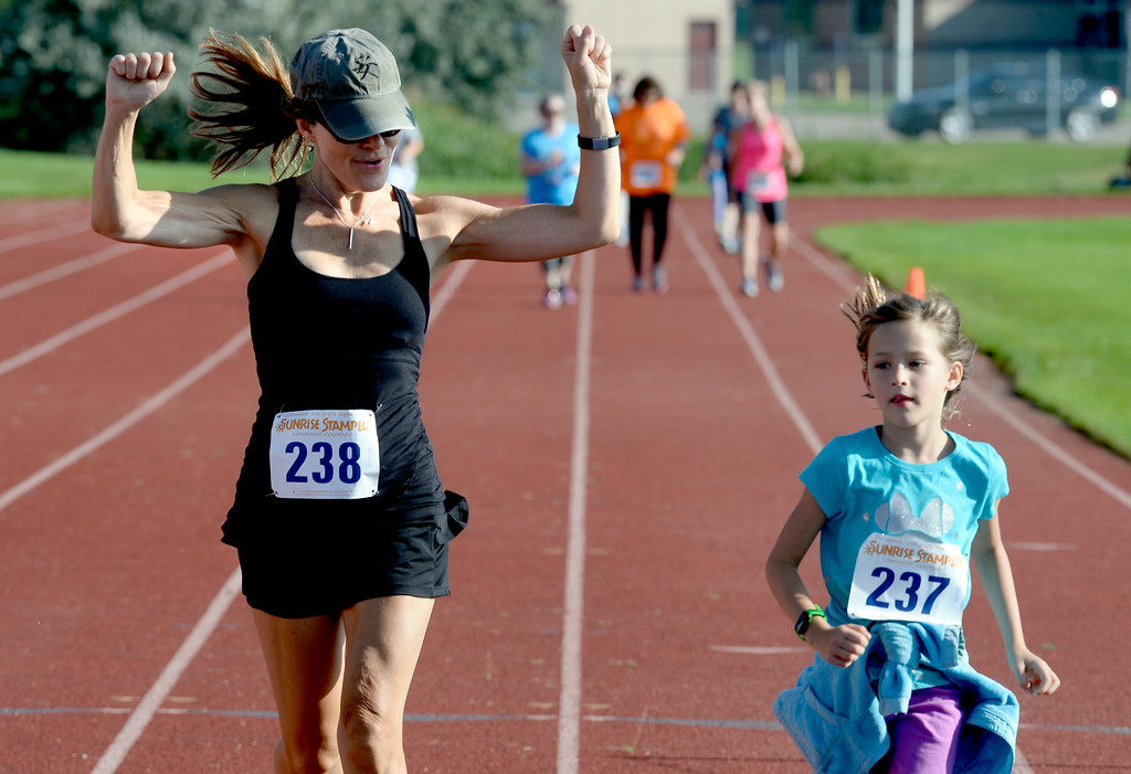 . Mary Huron-Hunter celebrates the end of the 2-mile race with her daughter, Vivienne, 7, during the annual Sunrise Stampede 2-mile and 10K  races held at Silver Creek High School in Longmont.  For more photos, go to dailycamera.com.  Cliff Grassmick  Staff Photographer August 12, 2017