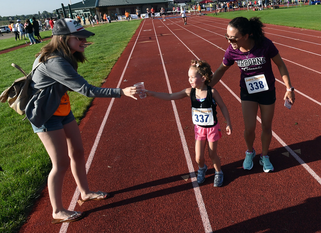. Larah Majeske, 6, gets a drink along side her mother, Mari, during the annual Sunrise Stampede 2-mile race held at Silver Creek High School in Longmont.  For more photos, go to dailycamera.com.  Cliff Grassmick  Staff Photographer August 12, 2017