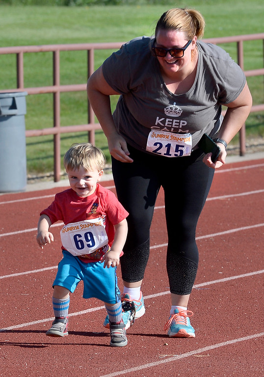 . Quinn Carton, 2, is turned loose by his mother, Jessica Hirsch-Carton, near the finish line of the 2-mile race of the annual Sunrise Stampede 2-mile and 10K  races held at Silver Creek High School in Longmont.  For more photos, go to dailycamera.com.  Cliff Grassmick  Staff Photographer August 12, 2017