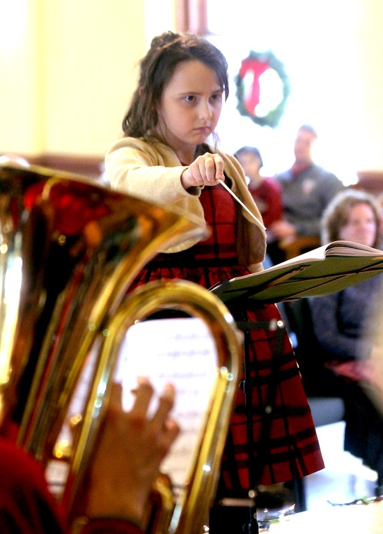 . Caleigh Russell 8, of Stratham NH and who\'s dad Patrick Russell plays Tuba in the group at Ayer Town Hall, fills in as conductor for the Annual Tuba Christmas Concert. SUN/ David H. Brow