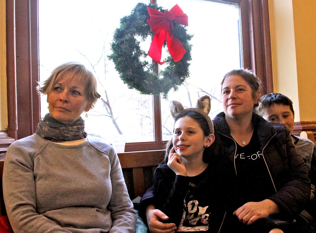 . Folks listen to the Annual Tuba Christmas Concert at the Ayer Town Hall, L-R, Michele Kosciak of Ayer, Morgan Smith 9, her mom Melanie Smith and brother Jacob Smith 11, of Bolton. SUN/ David H. Brow