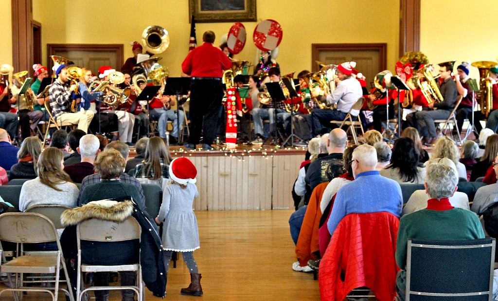 . Getting a better look for the Annual Tube Christmas Concert at the Ayer Town Hall is 5 year old Lucy Kennedy of Maynard. SUN/ David H. Brow