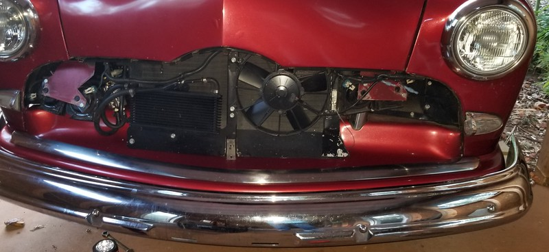 The transmission fluid cooler is located on the lower left of the grill area. The fluid first goes through the radiator heat exchanger, then to a 160 degree diverter valve that, when the fluid is below 160 degrees, diverts the flow back to the transmission. If the fluid is above 160 degrees, it sends the fluid to the cooler. It is located to the left of the cooler and to the right of the horns .