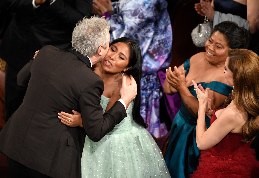 ". Yalitza Aparicio, right, congratulates Alfonso Cuaron in the audience as he is announced the winner of the award for best cinematography for ""Roma\"" at the Oscars on Sunday, Feb. 24, 2019, at the Dolby Theatre in Los Angeles. (Photo by Chris Pizzello/Invision/AP)"