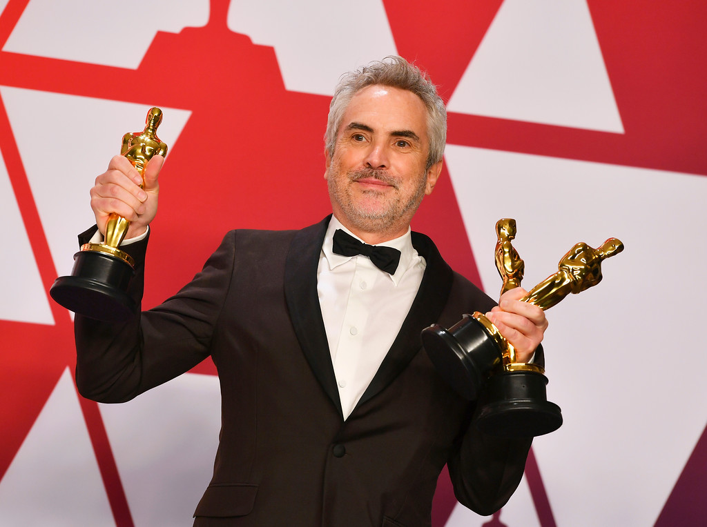 ". Alfonso Cuaron poses with the awards for best director for ""Roma\"", best foreign language film for \""Roma\"", and best cinematography for \""Roma\"" in the press room at the Oscars on Sunday, Feb. 24, 2019, at the Dolby Theatre in Los Angeles. (Photo by Jordan Strauss/Invision/AP)"