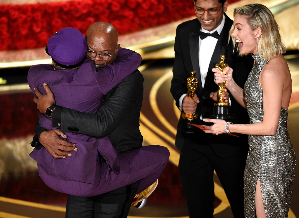 ". Samuel L. Jackson, center left, embraces Spike Lee, winner of the award for best adapted screenplay for ""BlacKkKlansman\"" as Brie Larson, right, looks on, at the Oscars on Sunday, Feb. 24, 2019, at the Dolby Theatre in Los Angeles. (Photo by Chris Pizzello/Invision/AP)"