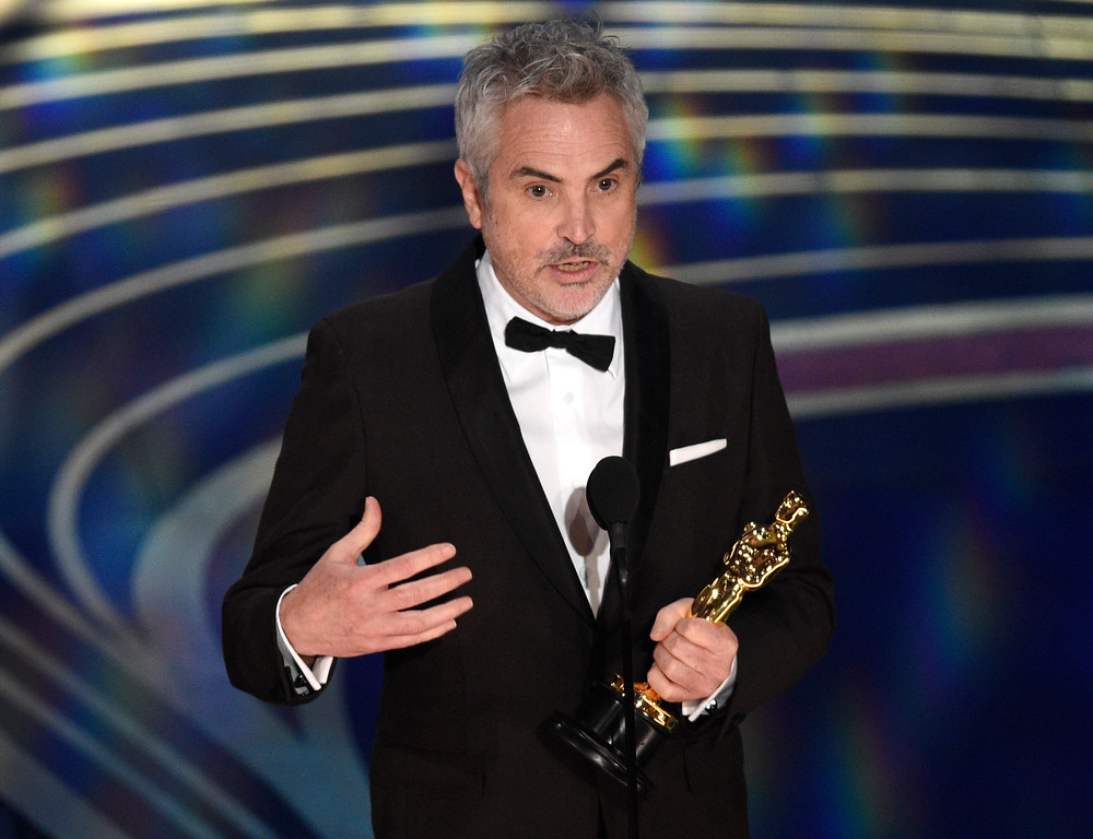 ". Alfonso Cuaron accepts the award for best cinematography for ""Roma\"" at the Oscars on Sunday, Feb. 24, 2019, at the Dolby Theatre in Los Angeles. (Photo by Chris Pizzello/Invision/AP)"