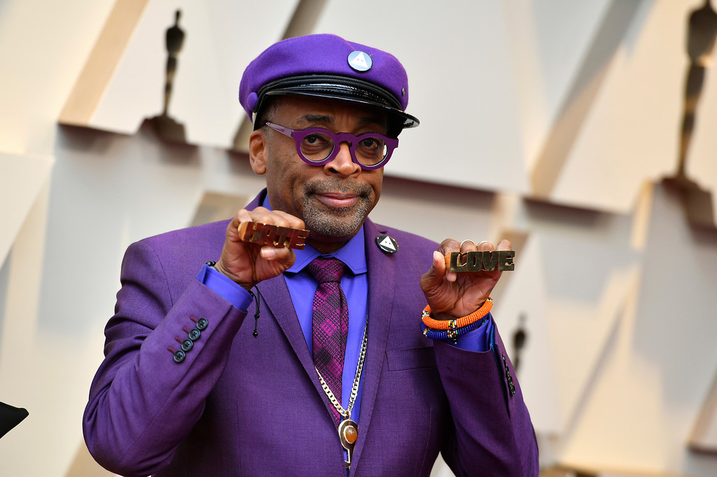 ". Spike Lee holds up brass knuckles reading ""hate\"" and \""love\"" from his iconic film \""Do The Right Thing\"" as he arrives at the Oscars on Sunday, Feb. 24, 2019, at the Dolby Theatre in Los Angeles. (Photo by Jordan Strauss/Invision/AP)"