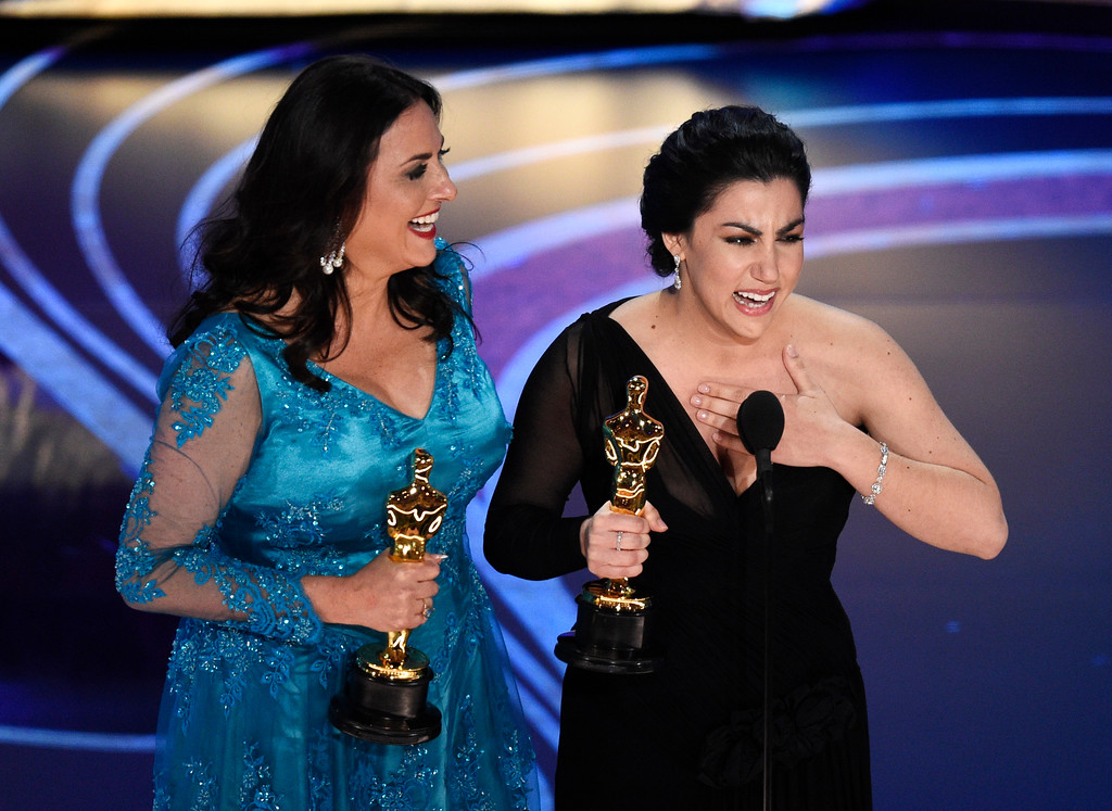 ". Melissa Berton, left, and Rayka Zehtabchi accept the award for best documentary short subject for ""Period. End of Sentence.\"" at the Oscars on Sunday, Feb. 24, 2019, at the Dolby Theatre in Los Angeles. (Photo by Chris Pizzello/Invision/AP)"