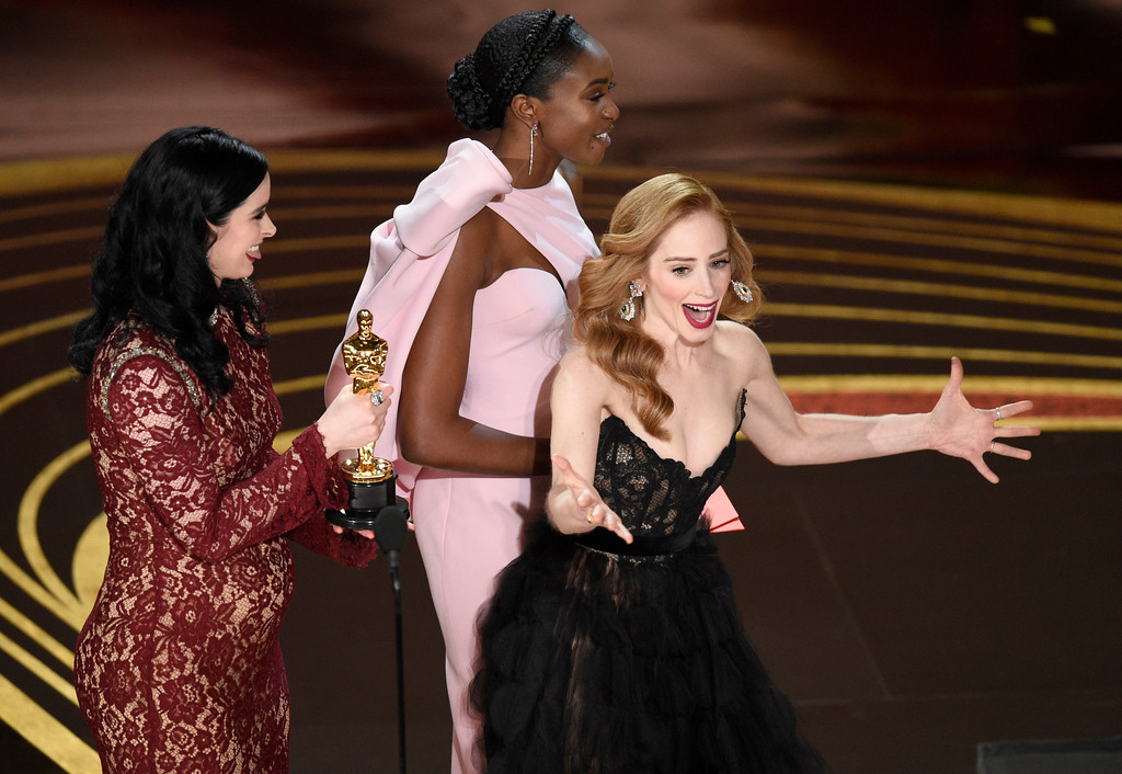 ". Jaime Ray Newman, right, reacts as Krysten Ritter, from left, and Kiki Layne present her with the award for best live action short film for ""Skin\"" at the Oscars on Sunday, Feb. 24, 2019, at the Dolby Theatre in Los Angeles. (Photo by Chris Pizzello/Invision/AP)"