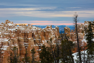 Warm light attempting to break through the thick cloud cover over Bryce