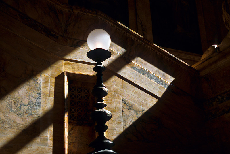 <b>Sunlight on Boston Library Steps</b> - The quiet steps on the old section of the Boston Public Library here have huge windows where the afternoon sun shines through.  Ironically, the only place where the light was hitting at this time was on the lamp.