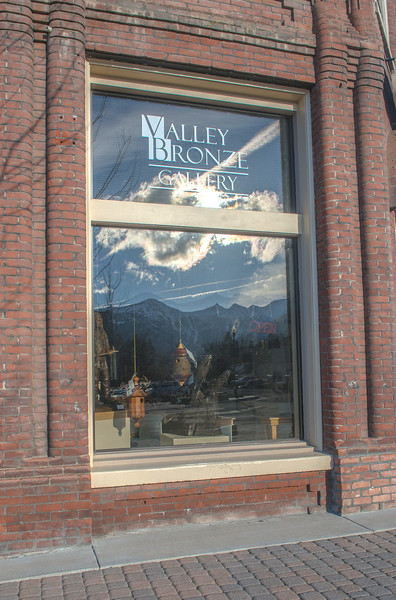 The Wallowa Mountains and downtown Joseph are reflected in the window of Valley Bronze's gallery on South Main Street.