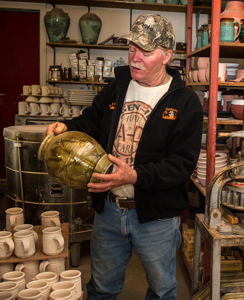Ceramic artist Ted Juve examines a recently-fired stoneware vase at his studio on Alder Slope, west of Enterprise. He still lives in the house where he grew up; his studio occupies a barn that his father built.