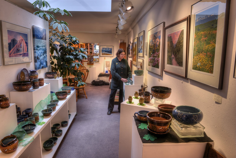 Mary Swanson, owner of The Bookloft bookstore, straightens a display of Ted Juve's potter amid David Jensen's photographs.  The Skylight Gallery, on Main Street in Enterprise, is part of the Bookloft, and was the first art gallery in Wallowa County.