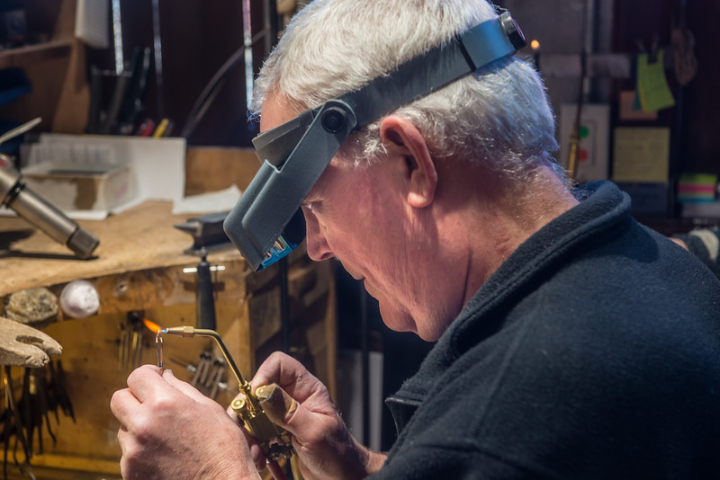 """Jewelry artist Stewart Jones puts the finishing touches on a set of fire-opal ear-rings  for a client in New York.   His clients hail from Australia, Germany, and Japan.  I've never been busier than I have been since I moved to Joseph, """" he said."""