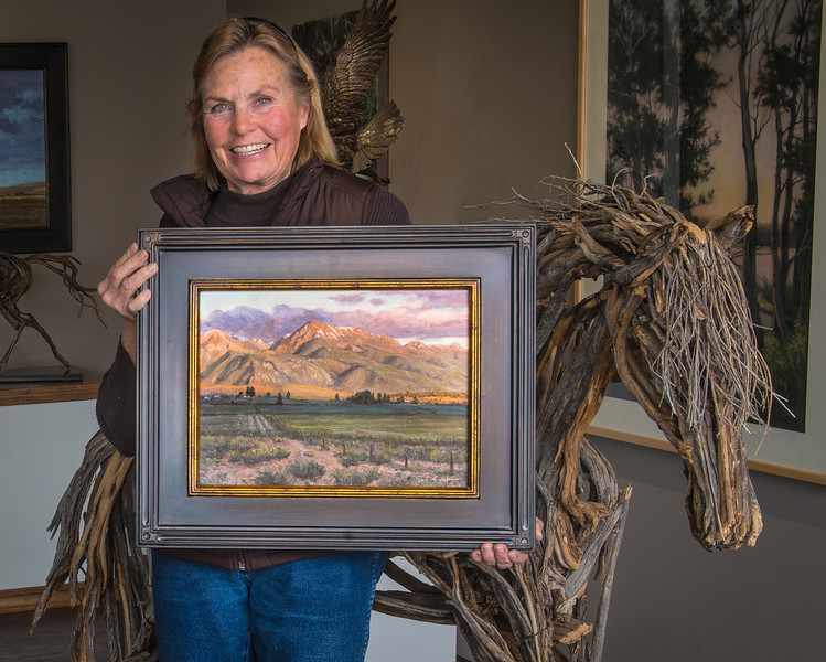"""Oil painter Leslie Leviner holds a recent painting in the Phinney Gallery of Fine Arts in Joseph.  A horsewoman who loves the outdoors, Leviner paints her landscapes on location in a style and school known as En Plein Air painting-- French for """"In the open air."""""""