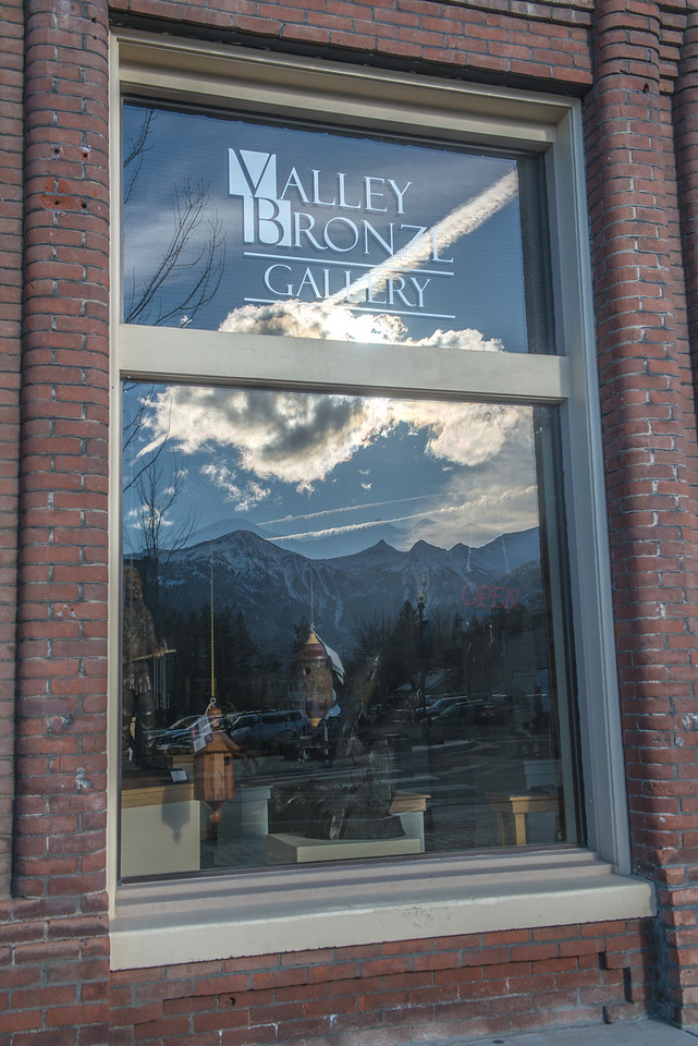 The Wallowa Mountains and downtown Joseph are reflected in Valley Bronze's gallery window on Joseph's South Main Street.