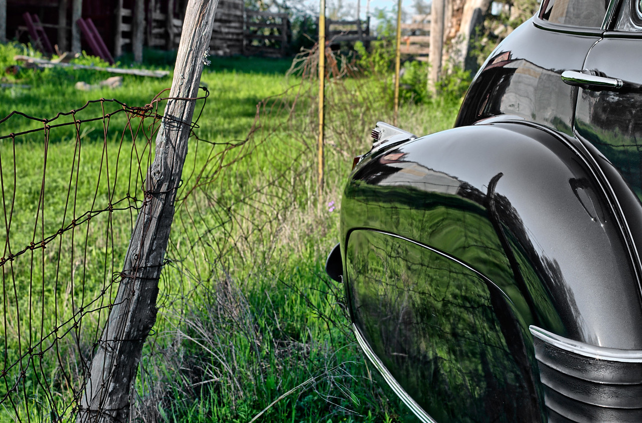 Rear fender of 1941 Cadillac and a country fence.