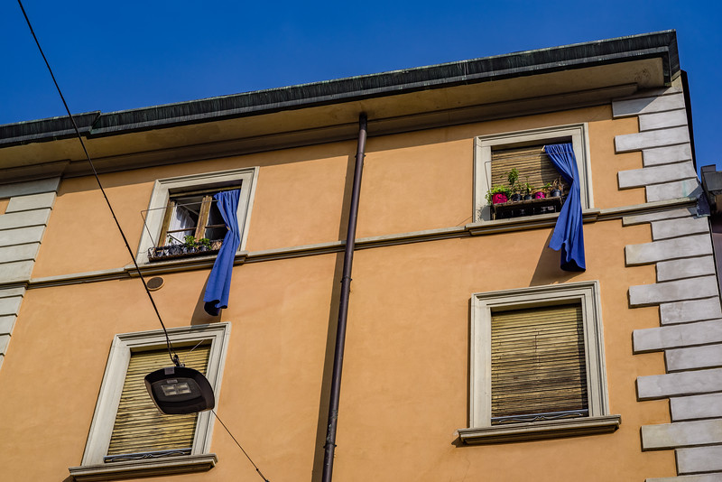 Blue curtains against an earth-tone-orange building, with coarsely textured wooden shutters and a brown rain spot in Milan. Love it!