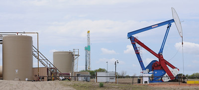 A oil well pumps on a pad east of Williston, N.D., on Thursday, June 6, 2013, as a rig roughly a half-mile to its west drills a new well. Photo by Dustin Monke / Forum News Service