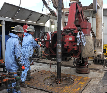 Floorhands work through cold temperatures and whipping winds on the floor of  Whiting Petroleum Corp. oil drilling rig southwest of Belfield, N.D., on Monday, April 22, 2013.