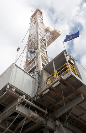 A North Dakota state flag waves in the wind from the floor of a drilling rig operated by Whiting Petroleum Corp. southwest of Belfield, N.D., on April 22, 2013.