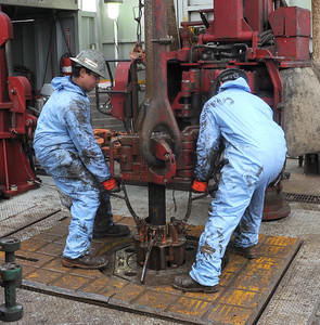 Floorhands remove pipe on the floor of Whiting Petroleum Corp. oil drilling rig southwest of Belfield, N.D., on Monday, April 22, 2013.
