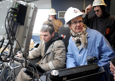 Charlotte Jacquemart, a reporter for the New Zurich Times in Switzerland, listens to a worker while visiting the doghouse, or drilling control room, on a Whiting Petroleum Corp., oil drilling rig southwest of Belfield, N.D., on Monday, April 22, 2013. Driller Brent Hanson of Bismarck, N.D., left, sits at the control of the rig while company hand and contractor Nevin Larsen of Alexander, N.D., right, watches from behind.