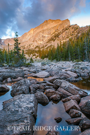 Stones and water below a sunrise on Hallet Peak