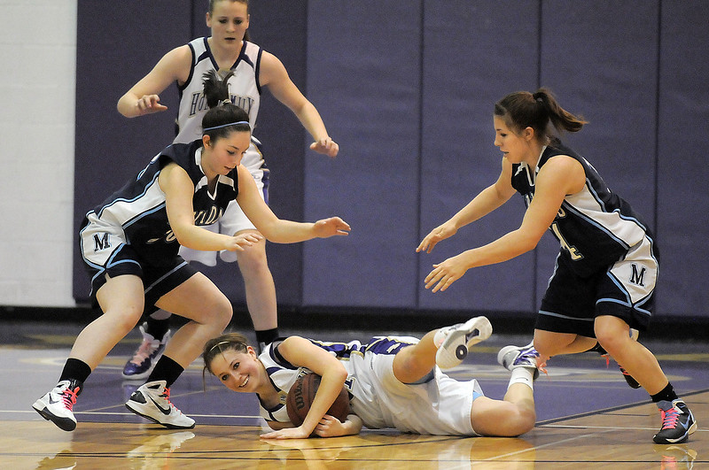 Holy Family's Sarah Talamantes smiles as she grabs a loose ball from Trinidad's Kendra Torrez and Justine Gallegos during the Class 3A sweet 16 game at Holy Family on Saturday.<br /> March 5, 2011<br /> staff photo/David R. Jennings