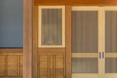 The wooden sliding entrance doors and window of a traditional Japanese home made from detailed pine carpentry.