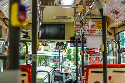HIROSHIMA - 15 JULY 2016: The driver of the sightseeing Maple Loop Bus checks his mirrors while waiting at a bus stop in downtown Hiroshima.