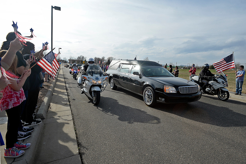 . Lovelanders and Immanuel Lutheran Church congregation members line the street and wave Amercian flags as a hearse carrying the body of U.S. Marine Riley Schultz arrives at Immanuel Lutheran Church on Thursday, March 28, 2019, in Loveland. (Photo by Jenny Sparks/Loveland Reporter-Herald)